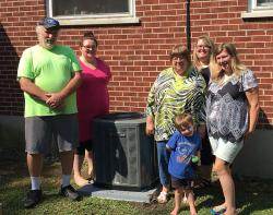 Brenda and her family with the new air conditioner