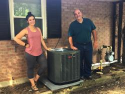 Kayleigh and her dad with her new air conditioner