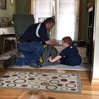 Rob shows Stefanie's son how he cleans ducts
